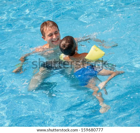 Father teaching his son to swim in the pool - stock photo