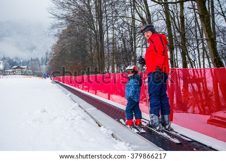 Father teaching skiing his happy little son during a winter vacation in Alpine ski resort in Austria. Little kid having fun and going up to the slope on the magic carpet lift. - stock photo