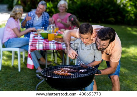 Father teaching son cooking on barbecue with family in background - stock photo