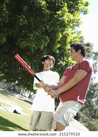 Father teaching son (10-12) how to hold baseball bat, standing on grass in park, smiling (tilt) - stock photo