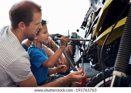 father teaching son how to use tools - stock photo