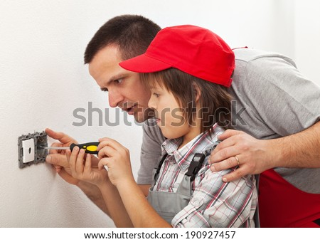 Father teaching son the basics of electrical work around the house - stock photo