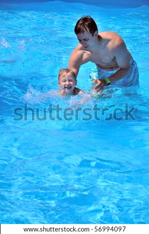 father teaching son to swim, he almost can do it - stock photo