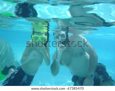 Father teaching son underwater safety hand signals for SCUBA diving - stock photo