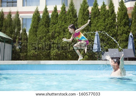 Father throwing daughter into the pool - stock photo
