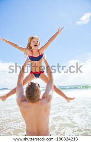 Father throwing happy smiling young daughter in air at beach with water and sky in background - stock photo