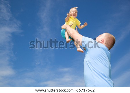 Father throwing his daughter in the air - stock photo