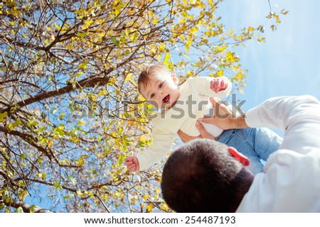 Father throwing his kid up in the air  in the autumn park. View through the dad's shoulder.  - stock photo