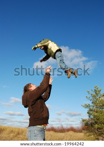 Father throwing his son - stock photo