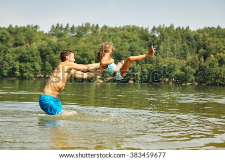 Father throws daughter in the water at the lake in summer - stock photo