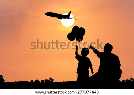 father use hand point to   the airplane on the sky at sunset his son see - stock photo