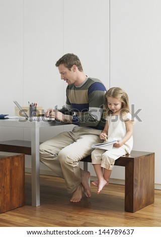 Father using laptop by daughter as she draws at home - stock photo