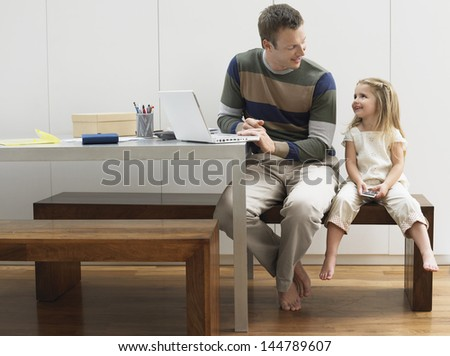 Father using laptop by daughter with cellphone at home - stock photo