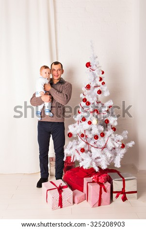 Father with a baby near Christmas tree. Concept of happy childhood. Celebrating Christmas in a homely atmosphere. Father dabbles with the child, laughing merrily.Merry Christmas. Family celebration. - stock photo