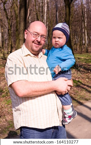 Father with a little son on a walk in the park - stock photo