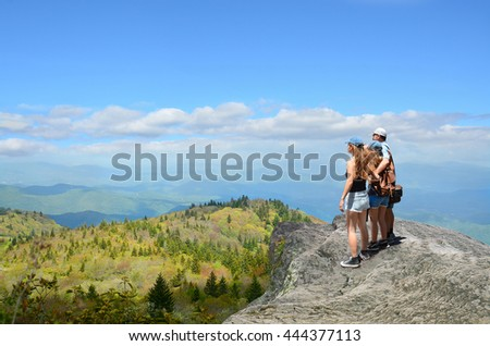 Father with arms around his family looking at beautiful summer mountains landscape, on hiking trip. People standing on  top of  mountain rock. Blue sky in background. North Carolina, USA. Copy Space. - stock photo