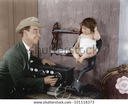 Father with baby in speaker horn of old radio - stock photo