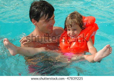 Father with child in water pool - stock photo