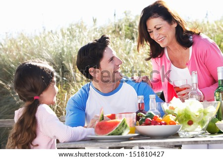 Father With Daughter And Grandmother Enjoying Outdoor Barbeque - stock photo