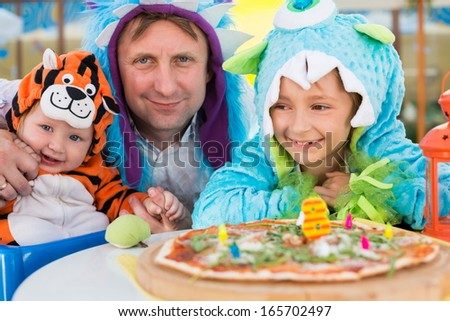 Father with daughter in monster costumes and baby boy in tiger costume celebrate the birthday in a cafe with pizza - stock photo