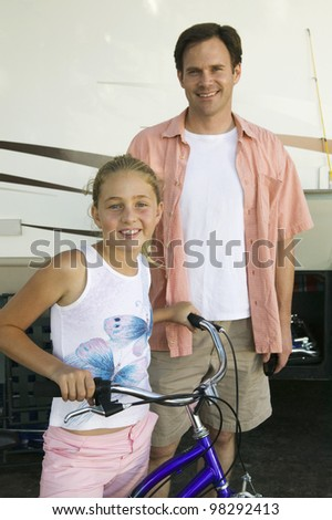Father with Daughter on Bike Next to RV - stock photo