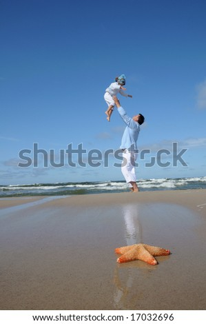 Father with daughter on the beach - stock photo