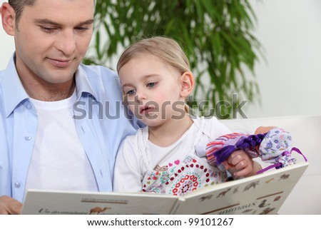 Father with daughter reading book - stock photo