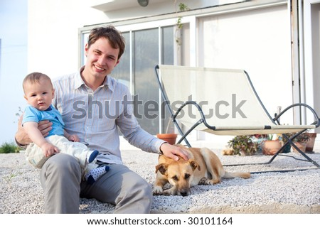 father with his baby son and dog in front of a house - stock photo