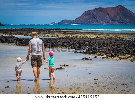 Father with his children, little boy and girl, walking in water waiting for wave to come on the beach in summer - stock photo