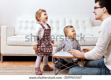 father with his little children in the house, soffa on background. - stock photo