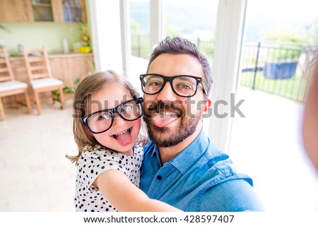 Father with his little daughter sticking tongue out - stock photo