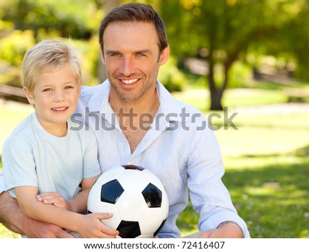 Father with his son after a football game - stock photo