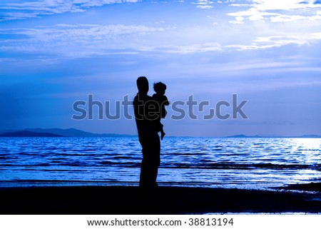 Father with his son by the beach - silhouette - stock photo