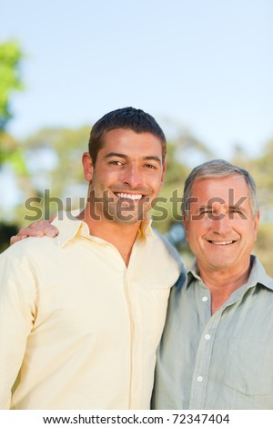 Father with his son looking at the camera in the park - stock photo