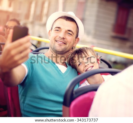 Father with his son traveling by tour bus and taking selfie - stock photo