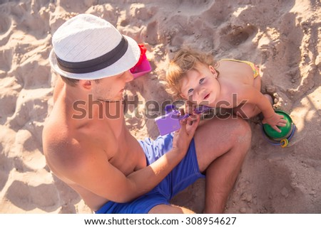 Father with little daughter on beach - stock photo