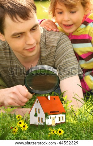 father with little girl looking on small house through magnifier collage - stock photo