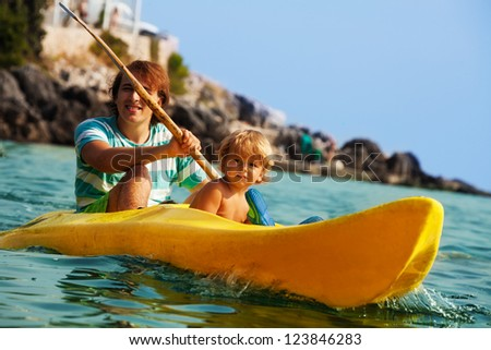 Father with little son rowing on the kayak in the sea - stock photo