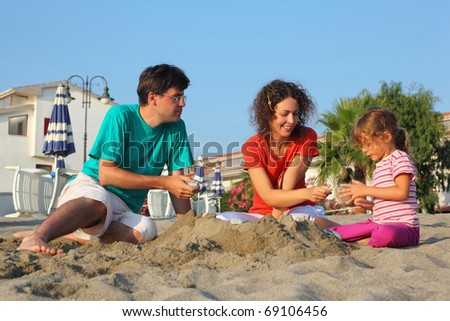 Father with  mother and daughter sit on  beach in  day-time and play on sand - stock photo
