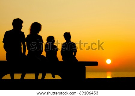 Father with mother and two children  sit on  bench on  beach in  evening and converse - stock photo