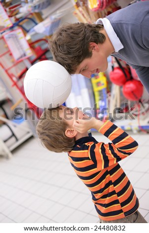 Father with son and ball in shop - stock photo