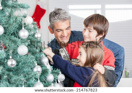 Father with son and daughter decorating Christmas tree. Family Christmas concept. - stock photo