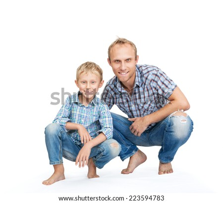 Father with son dressed in jeans and plaid shirts on the white - stock photo