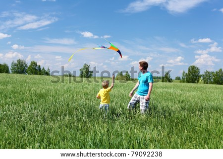father with son in summer playing with kite - stock photo