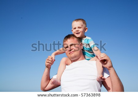 father with son on shoulders, sunny day, blue sky - stock photo