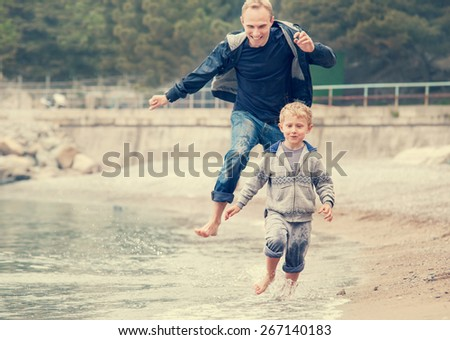Father with son running on the sea surf line - stock photo