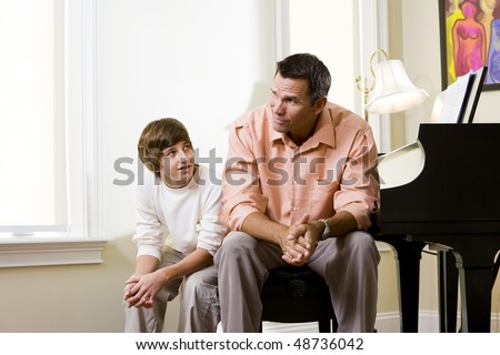 Father with teenage son at home sitting together on piano bench, boy looking up to dad - stock photo