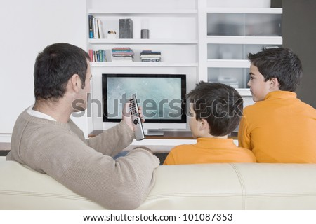 Father with twin brothers watching tv at home, using the control remote. - stock photo