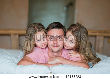 Father with two adorable little girls having fun in bed smiling - stock photo