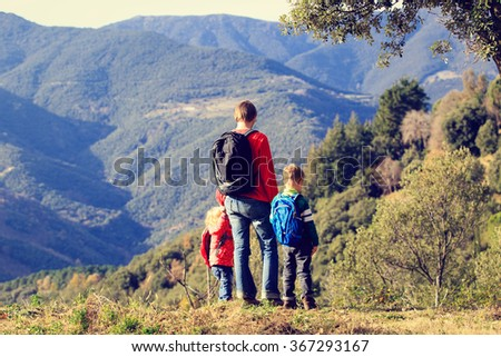 father with two kids travel in mountains - stock photo